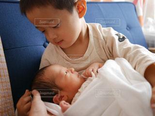とっても優しい眼差しで弟を抱っこする兄の写真・画像素材[1504248]