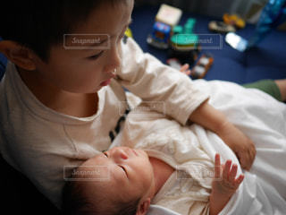 産まれたばかりの弟を抱っこする兄の写真・画像素材[1504250]