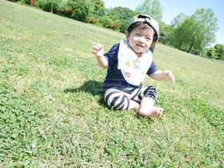 芝生に座っている小さな男の子の写真・画像素材[1515182]