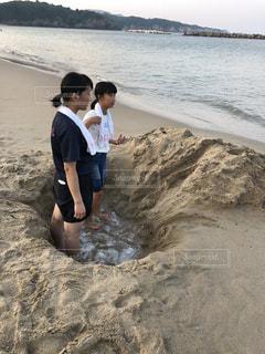 ビーチ(海岸)で穴掘りする姉妹の写真・画像素材[1541276]