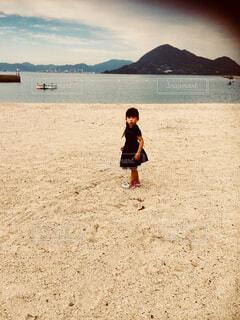 砂浜の上に立っている少女の写真・画像素材[1512949]