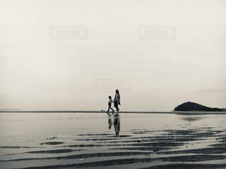 夕暮れの海岸を散歩する姉妹の写真・画像素材[2448728]