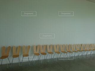 椅子の上に座っている木製のベンチの行の写真・画像素材[1519770]