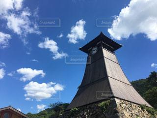 建物の側に時計と大きな背の高い塔の写真・画像素材[1511509]