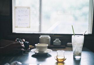 窓の前のテーブルに座っている人の写真・画像素材[1510056]