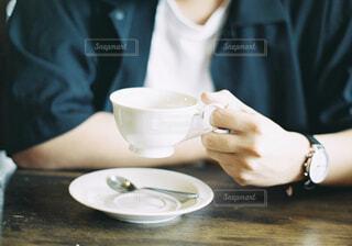 一杯のコーヒーをテーブルに着席した人の写真・画像素材[1610851]