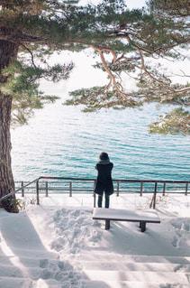 田沢湖をバックに立つ男性の写真・画像素材[1751174]