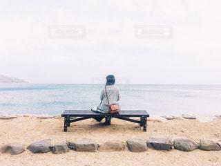 海を背景にベンチに座っている女性の写真・画像素材[1804911]
