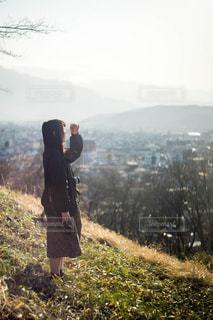 山の丘に立つ女性の写真・画像素材[1829959]