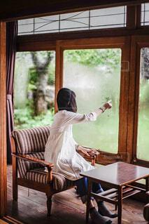 窓の前のテーブルに座っている女性の写真・画像素材[1864319]