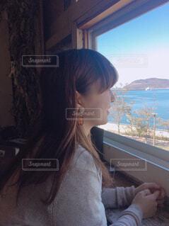 窓の前に座っている女性の写真・画像素材[1864476]