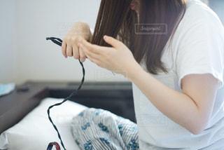 アイロンで髪を整えている女性の写真・画像素材[2131792]