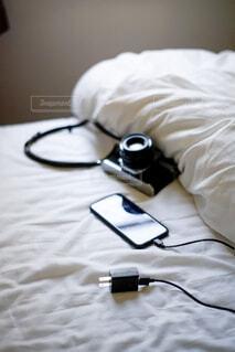 ベッドの上のスマとと充電器の写真・画像素材[2131793]