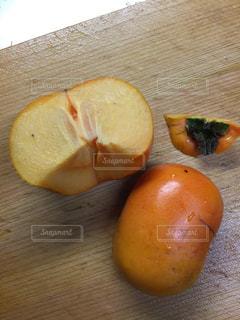 木製のまな板の上の半分に切ったたねなし柿の写真・画像素材[1512035]