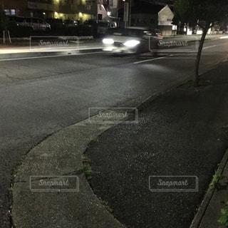 夜、ライトをつけて走り去る車。の写真・画像素材[1518317]