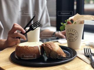 皿の上にケーキを置いたテーブルに座っている人の写真・画像素材[2323224]