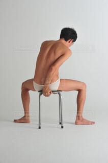 椅子に座ってポーズをとる男性の写真・画像素材[1515641]