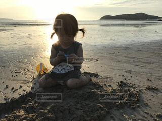 夕焼けビーチで砂遊びの写真・画像素材[1515810]