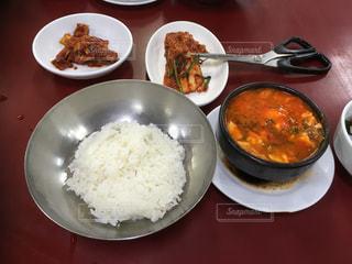 テーブルの上の皿の上に食べ物のボウルの写真・画像素材[1520130]