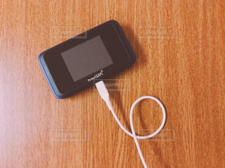 木製テーブルの上の携帯電話の写真・画像素材[1523092]