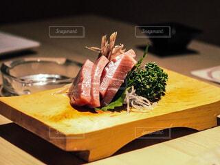 木製のまな板の上に食べ物のプレートの写真・画像素材[1525184]
