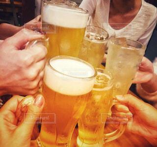 テーブルにビールのグラスを持っている手の写真・画像素材[1627137]
