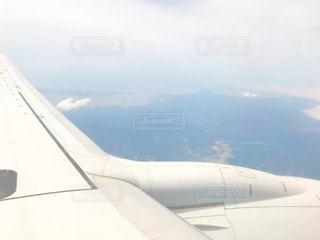 大きな飛行機が空中を高く飛んでいるの写真・画像素材[2140227]