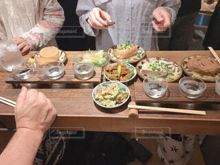 食べ物のあるテーブルに座っている人々のグループの写真・画像素材[2271797]