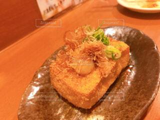 木製のテーブルの上に座っている食べ物の皿の写真・画像素材[2333342]