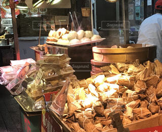 たくさんの食べ物でいっぱいの店の前に立っている人の写真・画像素材[2425062]