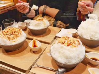 食べ物の皿を持ってテーブルに座っている人の写真・画像素材[2446906]