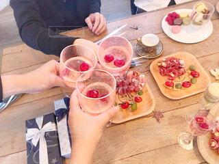 食べ物の皿を持ってテーブルに座っている女性の写真・画像素材[2807645]