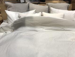部屋に座っている大きな白いベッドの写真・画像素材[3083373]