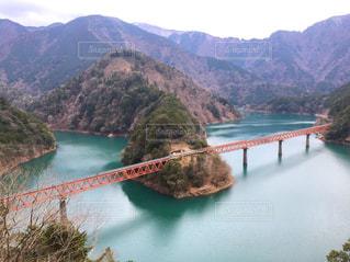 背景の山が付いている水の体の上の橋の写真・画像素材[1603399]