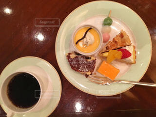 皿の食べ物とコーヒー1杯の写真・画像素材[2373754]