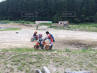 未舗装の道路をバイクに乗る子供たちの写真・画像素材[1542253]
