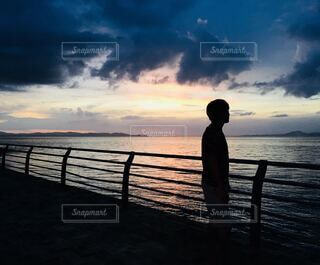 水の体に沈む夕日の前に立っている人の写真・画像素材[4692234]
