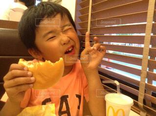ハンバーガーを食べる小学生の写真・画像素材[1541655]