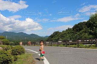 自然の中の道路に立っている男の子の写真・画像素材[1545668]