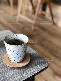 近くの木製のテーブルの上に座ってコーヒー カップの写真・画像素材[1545209]