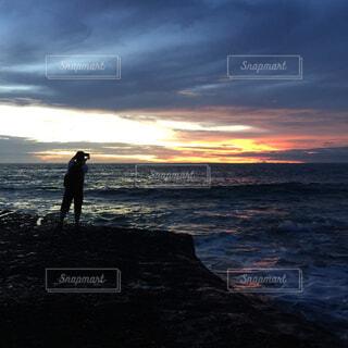 バック グラウンドで夕焼けのビーチに立っている人の写真・画像素材[1545617]