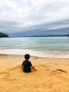 海の横にある砂浜のビーチの上に座っている人の写真・画像素材[1549512]