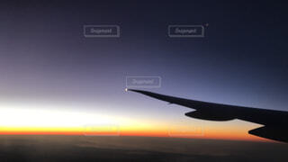曇りの青い空を飛んでいるジェット大型旅客機の写真・画像素材[1551514]