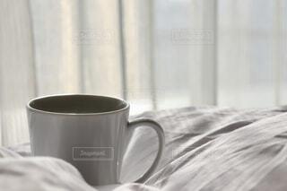 ベッドの上のコーヒーカップと朝日の写真・画像素材[1653999]