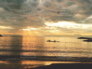 ビーチに沈む夕日とカヌーの写真・画像素材[1591574]