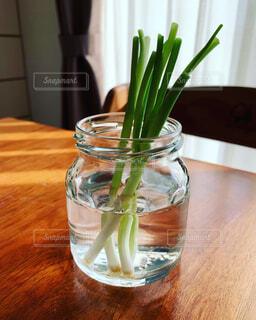 木のテーブルの上に座っている花で満たされた花瓶の写真・画像素材[3659908]