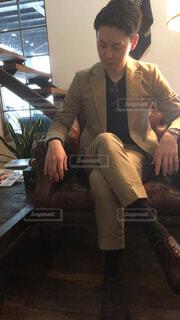スーツと椅子に座ってネクタイを身に着けている男の写真・画像素材[1646675]