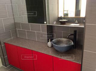 赤いカウンター洗面台と鏡の写真・画像素材[1857011]