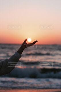 オレンジ色の夕日を持つ手の写真・画像素材[4123228]