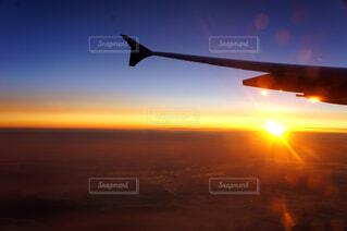 背景の夕日と空を飛んでいる飛行機の写真・画像素材[1585968]